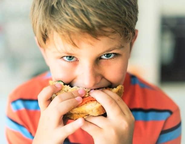 Niño comiendo bocadillo con camiseta roja